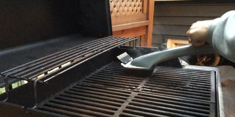 brush using steam to clean grate on grill