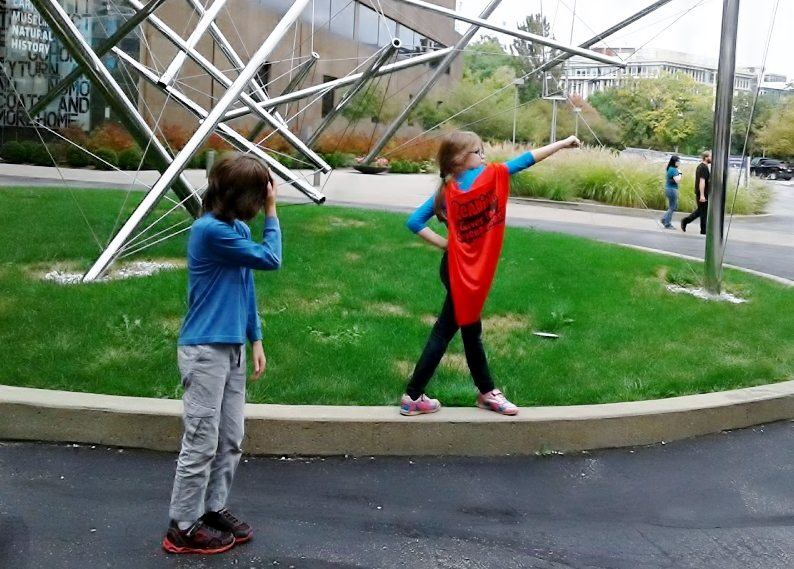 """Girl in """"Reading Gives You Superpowers"""" cape poses in front of an outdoor sculpture, her brother looks embarrassed."""