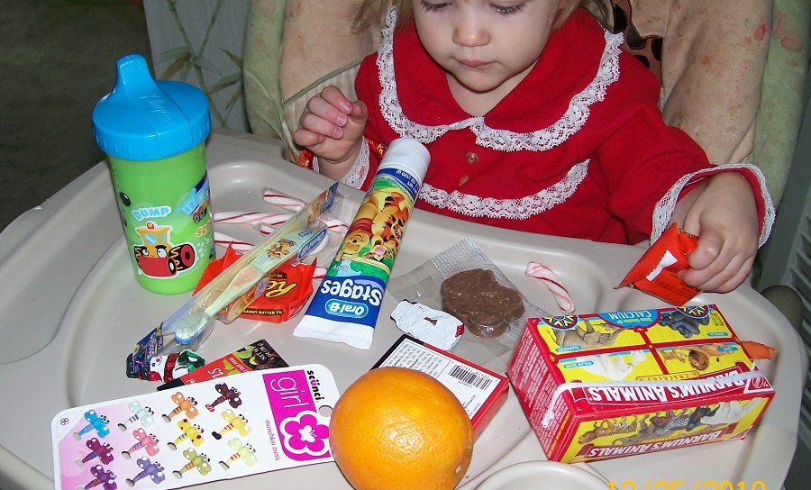 toddler with high chair tray full of stocking stuffers including chocolate, toothpaste, a toothbrush, barrettes, an orange, and animal crackers